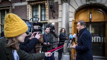 Een foto van Hugo de Jonge die de pers te woord staat over koopjesketens