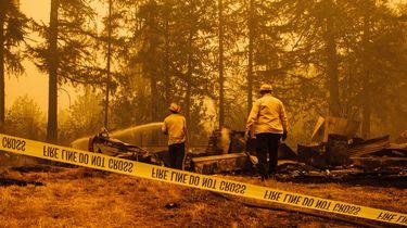 Op deze foto zijn Amerikaanse brandweerlieden te zien, ze staan achter een lint waarop staat 'fire line do not cross'.