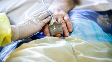 Een foto van een hand in latex handschoen die een andere hand met hartslagmeter eraan aanraakt
