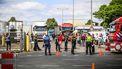 Een foto van politieagenten en handhavers op straat voor een slachterij met allemaal vrachtwagens.