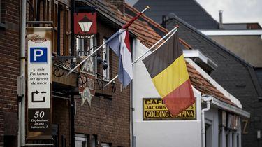 Een foto van vlaggen op de grens van Nederland en België