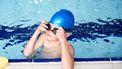 Een foto van een jongen die in een zwembad les krijgt