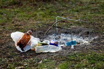 Een foto van afval zoals plastic flesjes bij een uitgebrand kampvuur op gras.