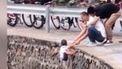 Op deze foto zie je een vader die zijn kind boven een afgrond laat hangen.