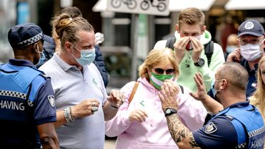 Een foto van handhavers die in Rotterdam checken of verplichte mondkapjes worden gedragen.