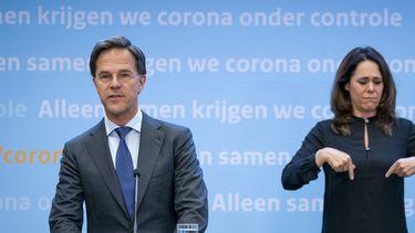 Een foto van Mark Rutte en tolk Irma Sluis tijdens de persconferentie