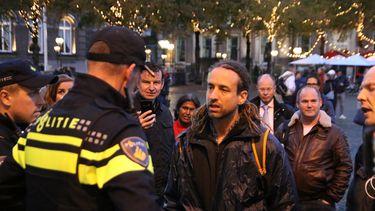 Op deze foto is Willem Engel te zien, hij staat met een groepje mensen tegenover politieagenten.