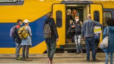Een foto van mensen die in een NS trein stappen.