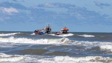 Een foto van twee reddingsboten op het water aan de kust