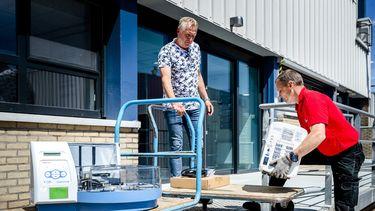 Een foto van twee mannen die testmachines van lage karren halen.