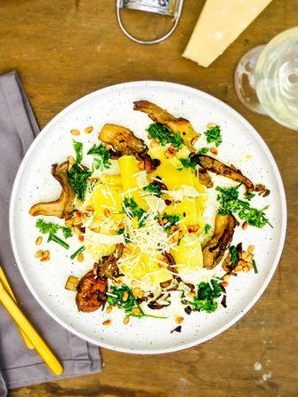 Op deze foto zie je open lasagne met paddenstoelen en groene kruiden