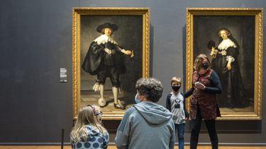 Op deze foto zijn mensen in het Rijksmuseum te zien, ze hebben mondkapjes op.
