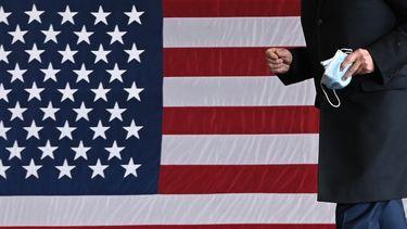 Een foto van de Amerikaanse vlag, Joe Biden staat ervoor met een mondkapje in zijn hand.