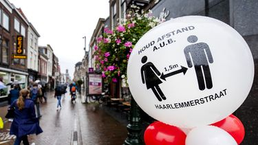 Een foto van een straat in Leiden met een waarschuwing om coronabesmettingen tegen te gaan