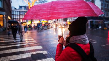 Vrouw met muts op straat onder paraplu met telefoon in de hand