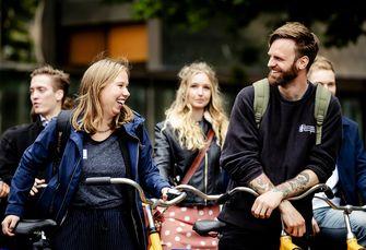 Op deze foto zie je vijfentwintig jongeren die fietsen onder aanvoering van tv-presentator Tim Hofman en Gert-Jan Segers (CU) van de Tweede Kamer naar het Catshuis.