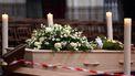 Een foto van een begrafeniskist met bloemen erop, er zit een rood met wit lint voor zodat niemand te dichtbij komt