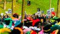 Een foto van een intocht met zwarte pieten, er staan demonstranten met borden langs de route