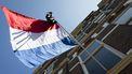 Een foto van een Nederlandse vlag aan een woning met een tas erbij, genomen van onderen. De vlag kan uit, want het is nationale slaagdag.