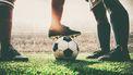 Foto van een voetbal en voetbalbenen