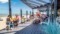 Een foto van een strandpaviljoen met klanten in de zon