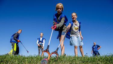 Deelnemers in Zaltbommel tijdens World Cleanup Day rapen zwerfafval. Beeld: ANP