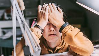 Op deze foto zie je een jonge vrouw met stress