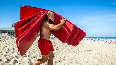 Een foto van een man op het strand met kussens voor strandbedden