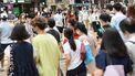 Een foto van een drukke straat in Hong Kong, iedereen draagt een mondkapje