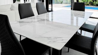 Een foto van een witte marmeren tafel met zwarte stoelen