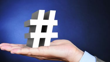 Een foto van het tekentje van de hashtag op een hand