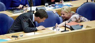 Premier Mark Rutte bekijkt de telefoon van minister Jeanine Hennis-Plasschaert van Defensie tijdens de Algemene Politieke Beschouwingen in de Tweede Kamer. Foto: ANP / Martijn Beekman