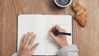vrouw schrijft op in boekje en eet een croissant