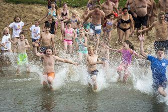 Een foto van kinderen die het water in rennen