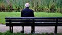 Op deze foto zie je een eenzame oude man op een bankje in het park zitten.