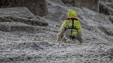Een foto van de zoektocht naar de surfers in het metershoge algenschuim bij Scheveningen