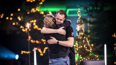 Twee mannen omhelzen elkaar.