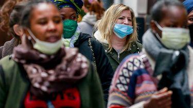 Op deze foto zie je mensen in een winkelstraat in Antwerpen met mondkapjes op.