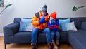Een foto van een man en een kind die het koud hebben in huis