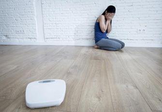 Een foto van een meisje met psychische problemen, zittend op de grond