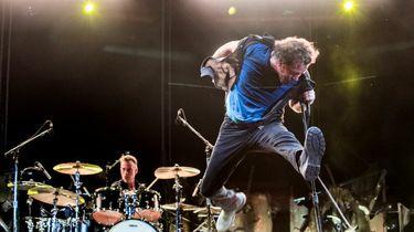 Een foto van een springende Eddie Vedder tijdens een liveconcert