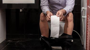 Een man op een toilet