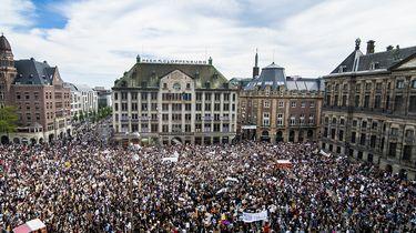 Op deze foto zie je protestanten op de dam.