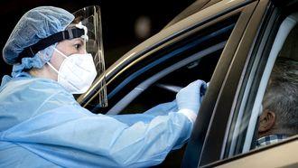 Een foto van een zorgmedewerkster die iemand in een auto test op het coronavirus