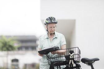 Op deze foto zie je een ouder persoon op een e-bike