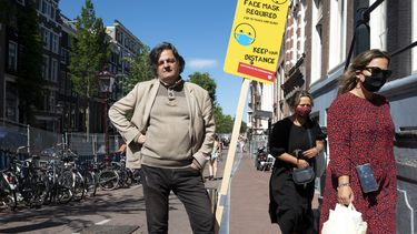 Een foto van Ab Gietelink bij een bord waarop staat dat je een mondkapje moet dragen