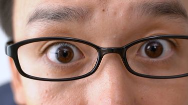 Op deze foto zie je een man die van heel dichtbij in de lens kijkt.