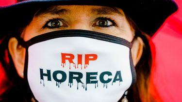 Een foto van een demonstrante met een mondkapje met de tekst RIP horeca