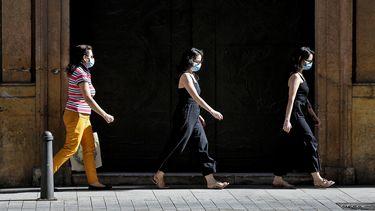 Een foto van mensen met mondkapjes in Spanje.