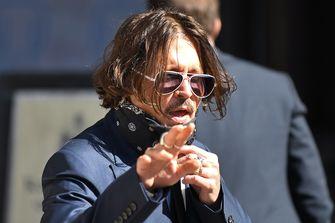Een foto van Johnny Depp die zwaait bij aankomst bij de rechtbank
